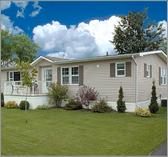 Light Brown Pristine Mobile Home With Bushes And Trees Around It.