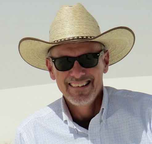 Man Wearing SUnglasses And A Straw Hat.