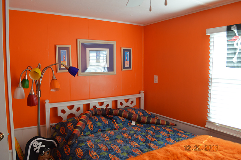 Bedroom With Bright Orange Walls With White Trim At The Bottom.