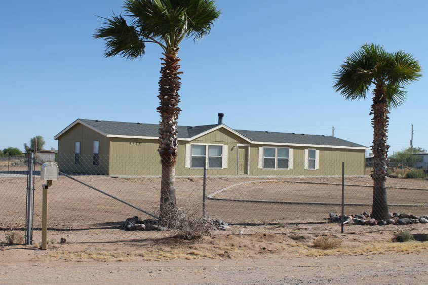 Green Mobile Home On A Dirt Lot With A Chain Link Fence Surrounding It.