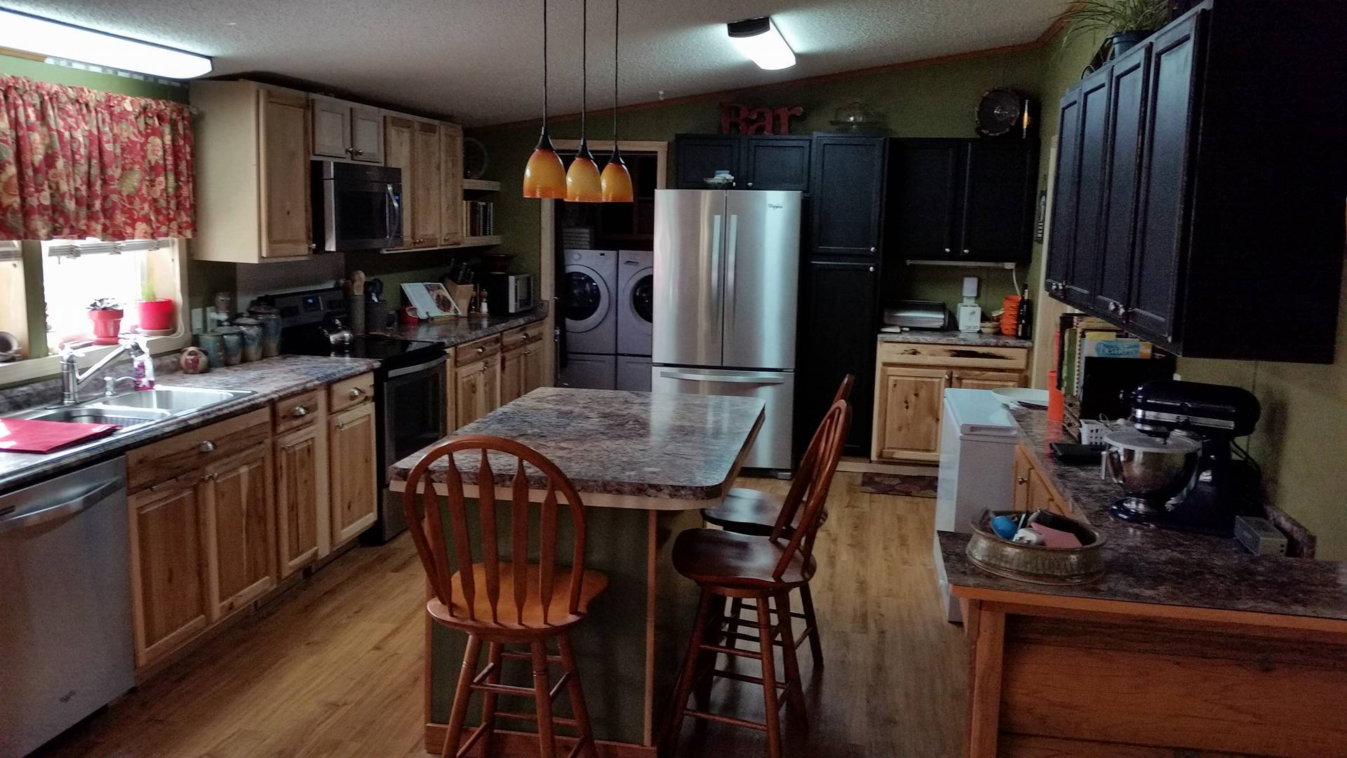 Kitchen With Stone Counter Tops And Black Cabinets On One Side And Wood Cabinets On The Other.