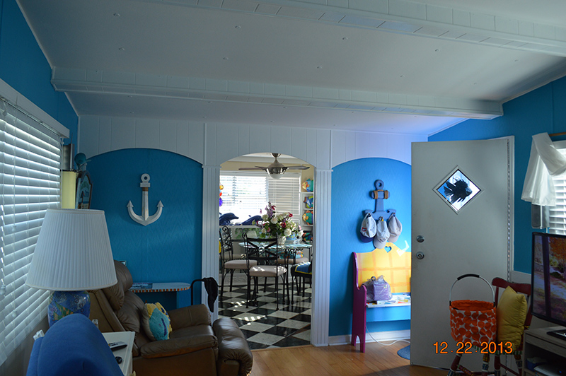 Living Room With Bright Blue Walls And Wood Flooring And Nautical Themed Accent Pieces.