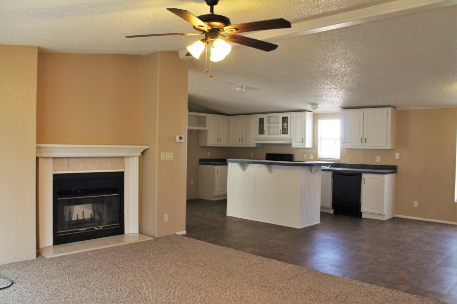 Fireplace With White Trim And The Kitchen With A White Island And White Cabinets.