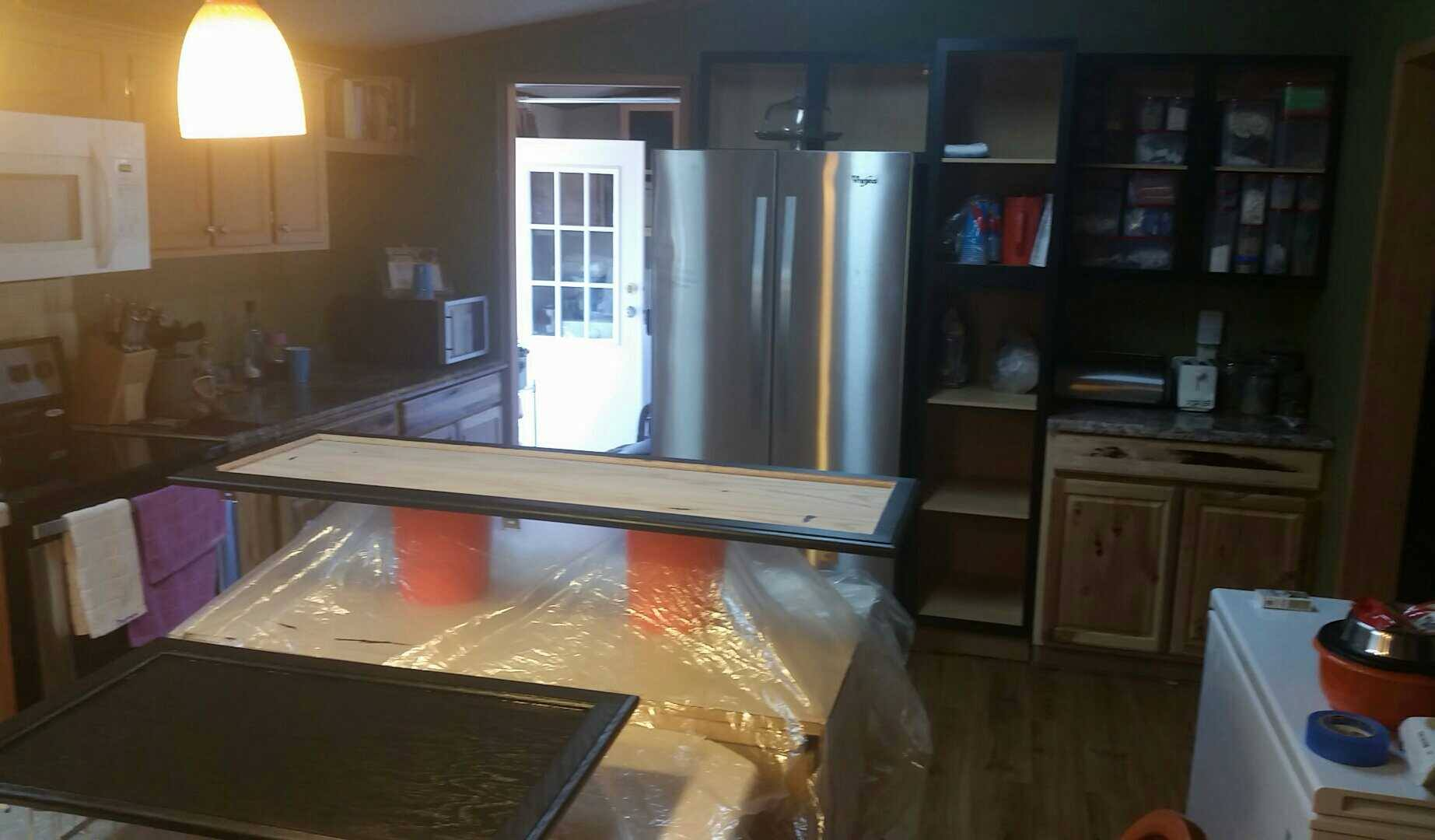 Kitchen Island With Cabinet Doors Beign Stained Black On A Plastic Drop Cloth.