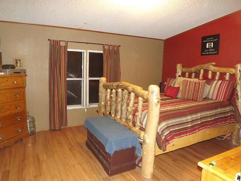 Bedroom With New Wood Floors, And Tan And Red Painted Walls.
