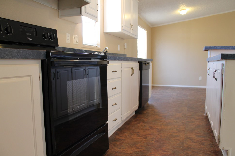 Close Up View Of Black Stove And White Cabinets With Blue Counter Tops.