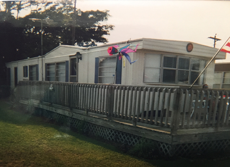 White Mobile Home With A Wrap Around Porch And Blue Shutters.
