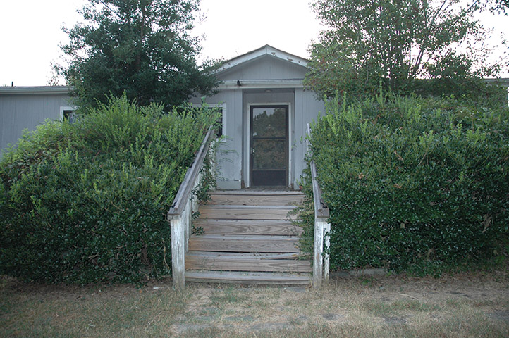 Grey Mobile Home With Overgrown Trees And Shrubs Growing Over The Edges Of The Damaged Porch.
