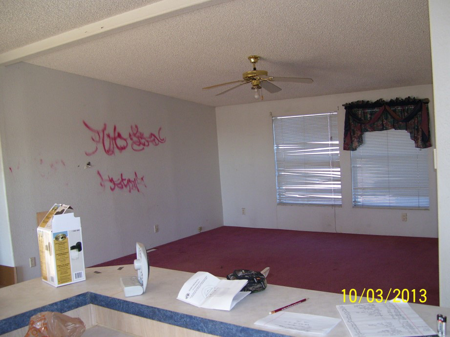 Living Room With White Walls With Red Graffit Spray Painted On, And Red Carpeting.