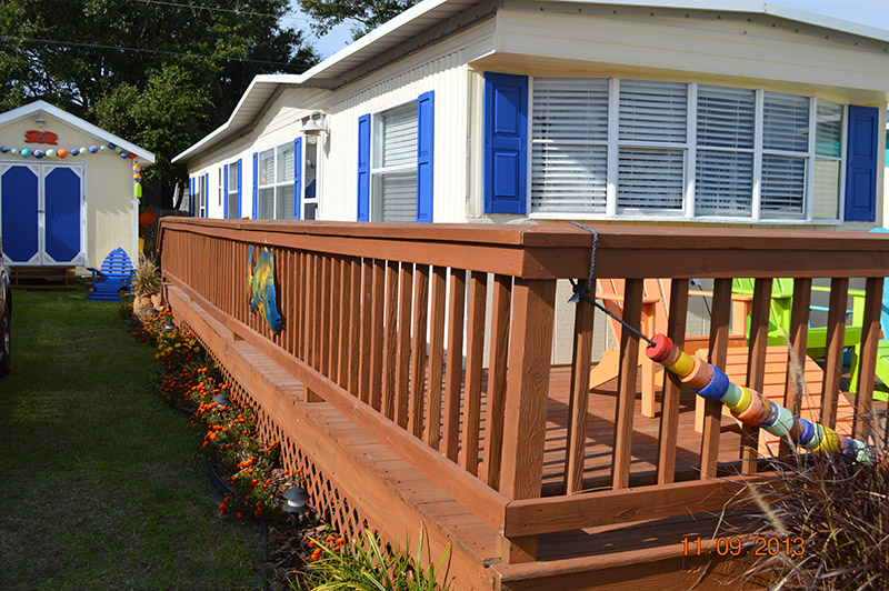 Newly Painted White Mobile Home With Blue Shutters And A Newly Painted Brown Porch Porch.
