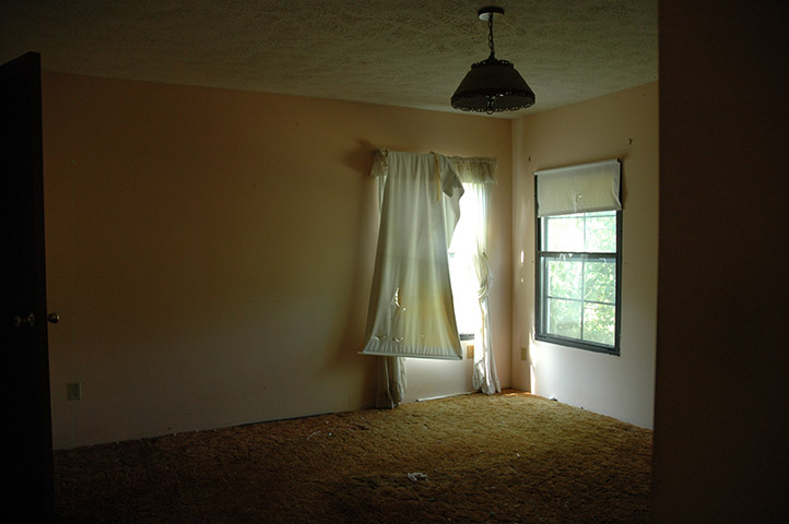Room With Torn And Stained Curtains And Orange Discolored And Stained Carpet.