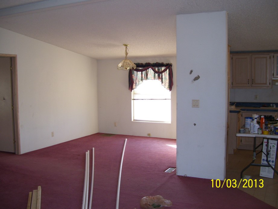 Dining Room With White Damaged Walls And Red Carpeting.