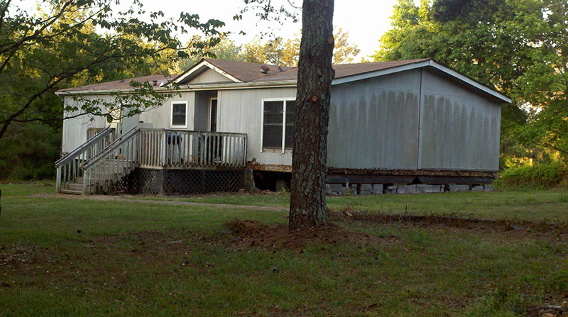 Side Of The Mobile Home With The Skirting Removed Showing The Rocks Used As The Foundation.