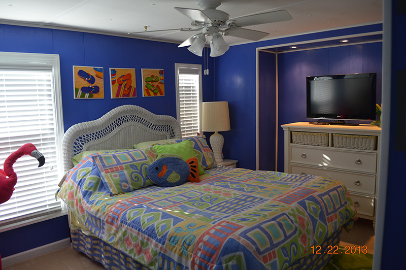 Bright Blue Walled Bedroom With White Accent Pieces And A Recessed Area Housing A Dresser And TV.