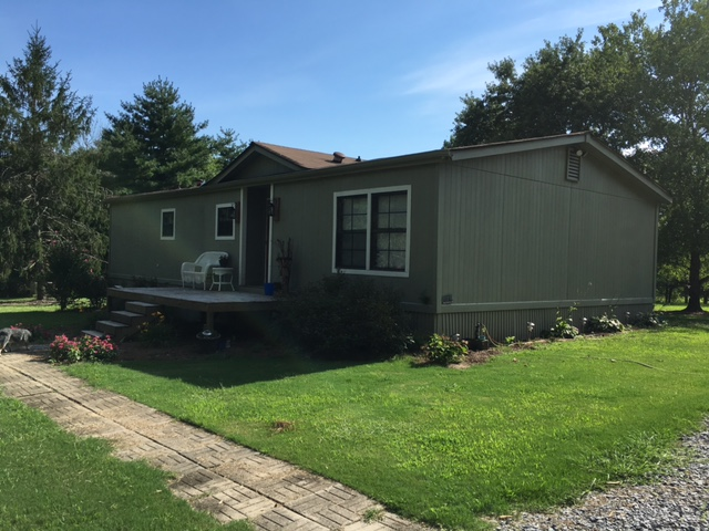 Side Of Green Mobile Home With Matching Green Skirting And Flowerbeds With Plants And Flowers.