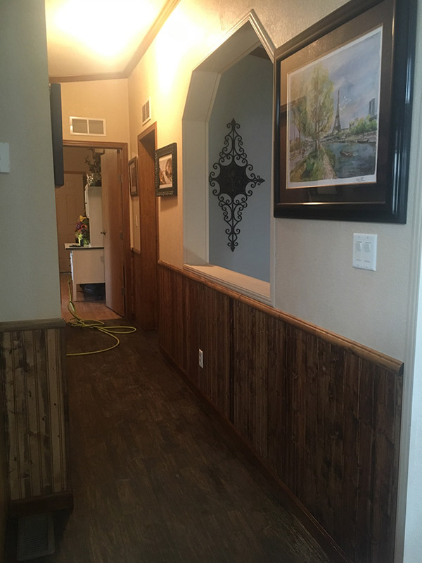 Hallway With The Walls Painted White At The Top And Wooden Wainscotting At The Bottom.