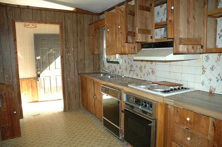 Kitchen With very Old Appliances, Vinyl Flooring, And Wood Paneling And Cabinets.