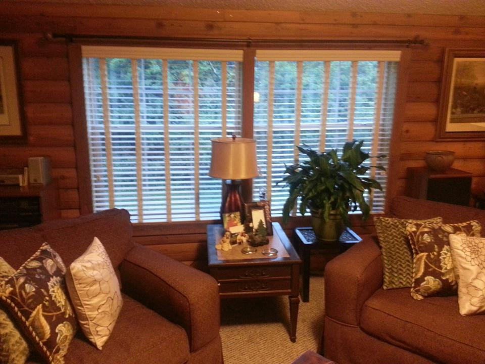 Living Room With Wood Walls And Custom Wood Blinds.