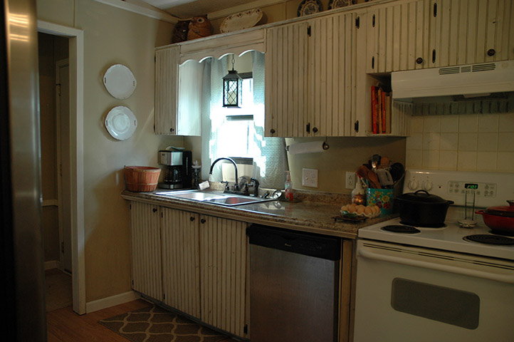 Kitchen With Updated Appliances, White Painted Wood Cabinets And Painted Walls.