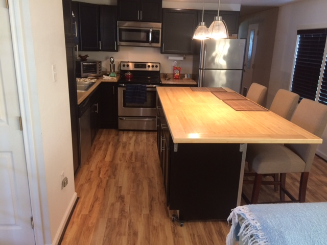 Updated Kitchen With New Wood Floors, A New Wooden Island And All New Black Cabinets.