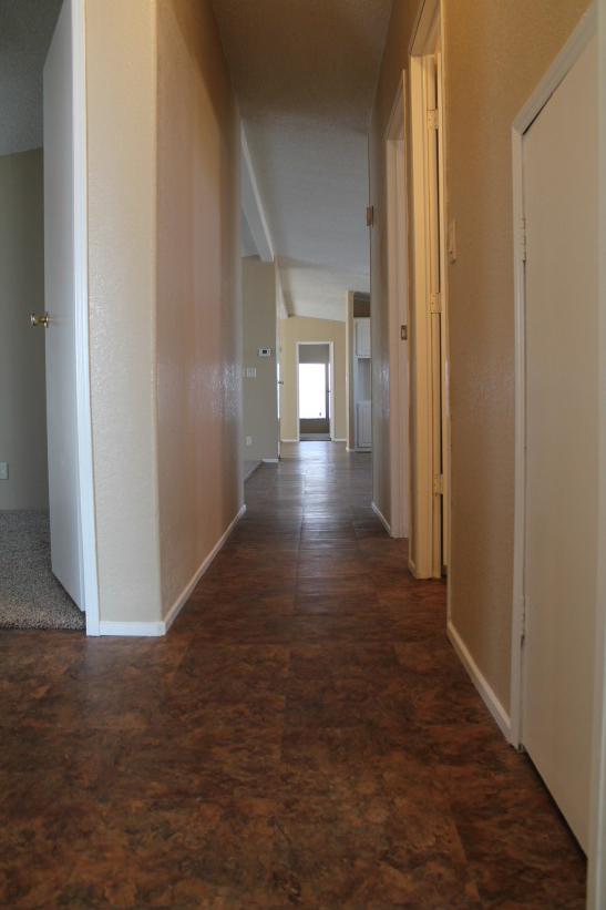 Hallway With New Brown Tile And Repaired Cream Colored Walls.