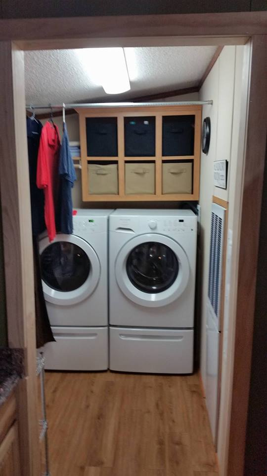 Laundry Room With Front Loading Washer And Dryer With Storage Above Them.