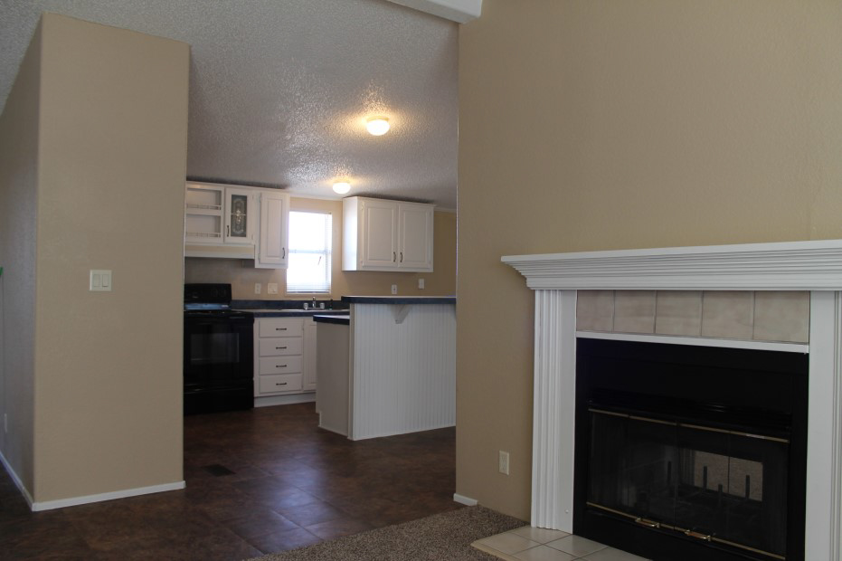 Living Room With White Trimmed Fire Places And The Kitchen With White Cabinets And A Black Stove.