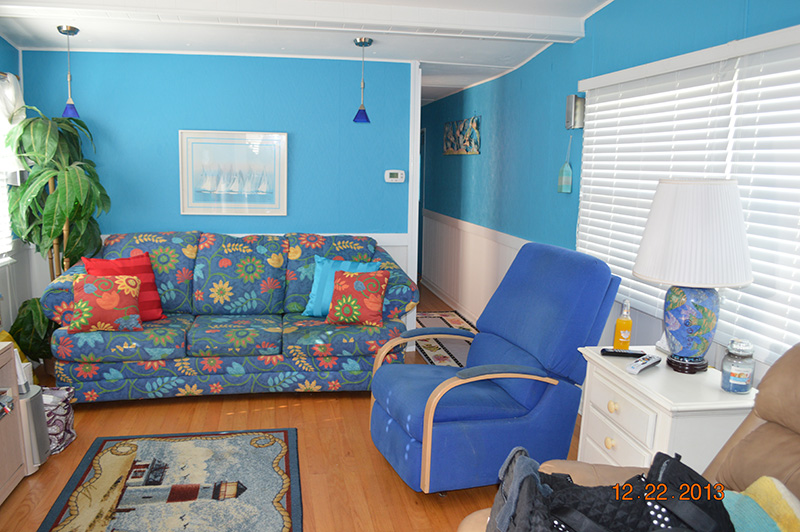 Living Room With Bright Blue Walls On The Top Half And White Paneling on The Bottom.