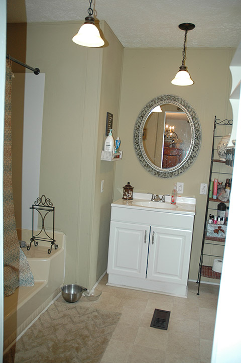 Updated Bathroom With Painted Walls, A New White Cabinet Under The White Sink And Tile Flooring.