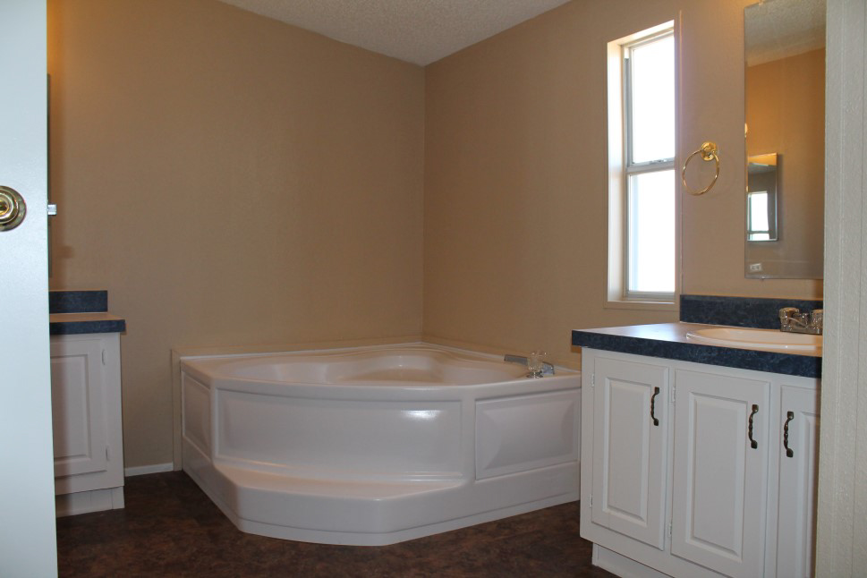 Bathroom With A Large Corner Tub Tan Walls, And White Cabinets.