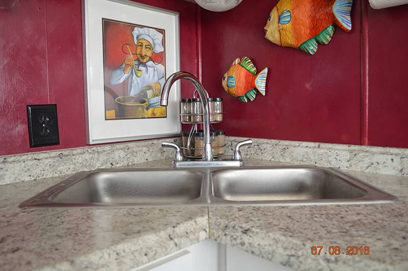 Stainless Steel Sink With Red Wall Behind It.