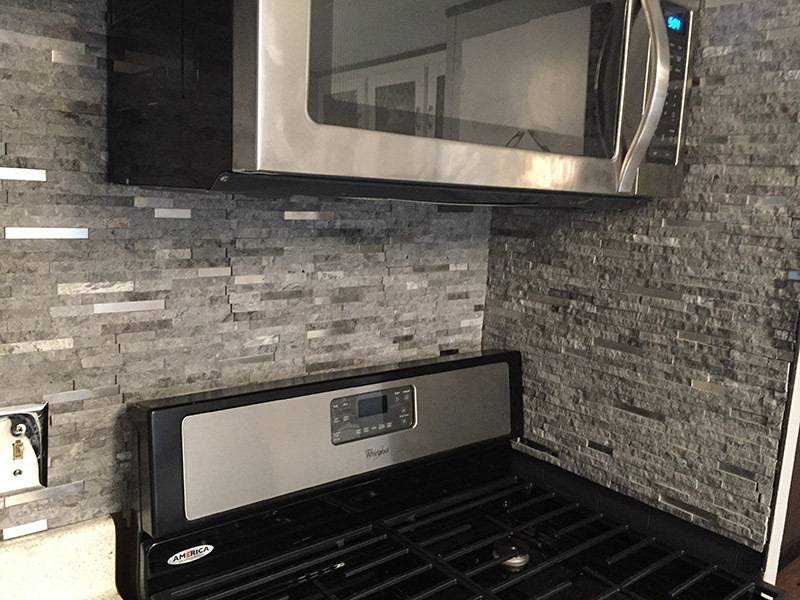 Black And Stainless Steel Stove, With Stone Backdrop On The Wall.