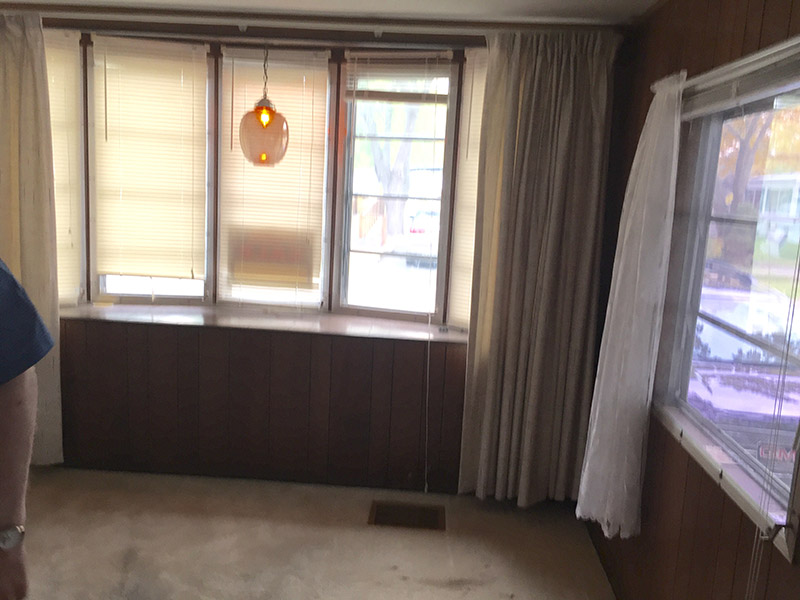 Room With Old White Carpeting And Aged Wood Paneling Below A Three Pane Window.