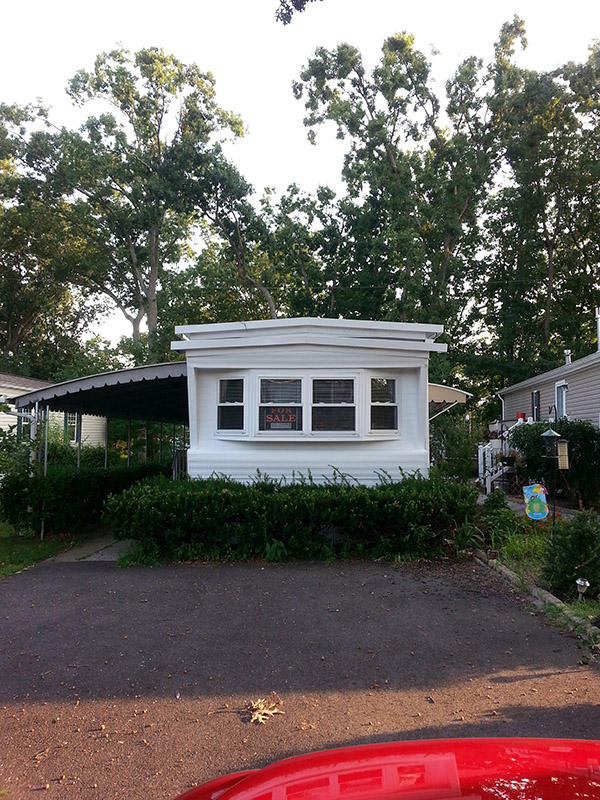 Outside Of A Mobile Home With Four Windows Across The Front And An Awning Over The Door.