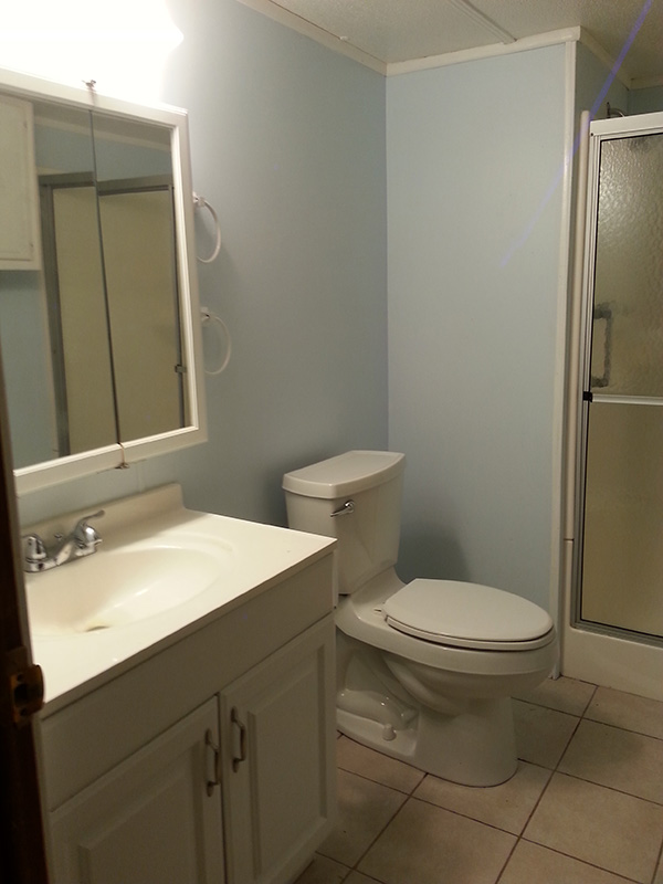 Bathroom With Blue Walls, White Sink, Toilet And Mirrors.