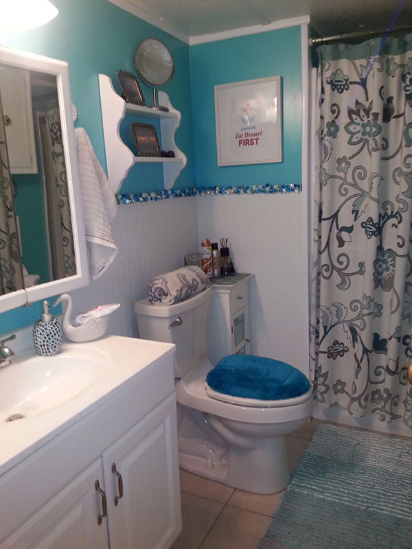 Bathroom With Bright Blue Walls At The Top, Sea Glass Separating The Blue From White Wainscotting.