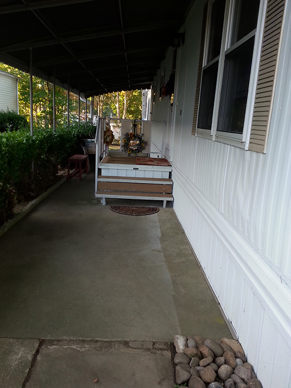 Front Door Area Of Mobile Home, With A Small Square Porch In Front Of The Door.