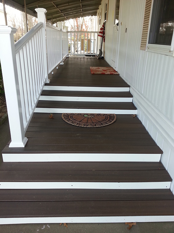 Front Of Mobile Home With A Large White And Brown Composite Porch And Walkway.