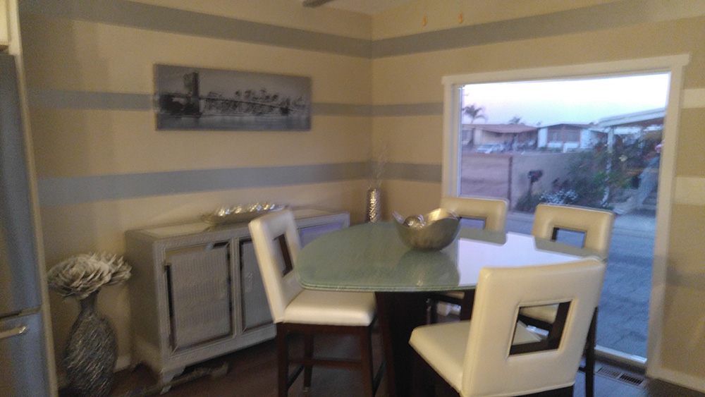 Dining Room With Beige Walls With Silver Horizontal Bands.
