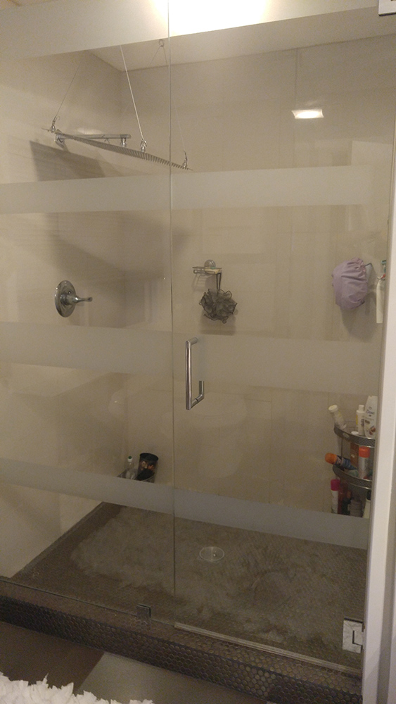 White tiled Shower With Full Glass Doors With Bands Of White Horizontally Across.