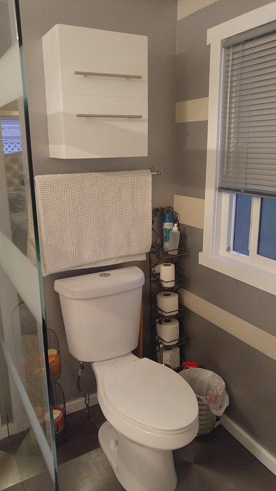 Another View Of the Bathroom, Showing The White Toilet And Cabinet, And Grey And White Banded Walls.