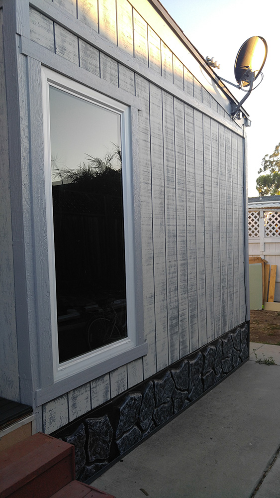 The Side Of A Mobile Home With Reil Rock Skirting and Distressed White And Grey Siding