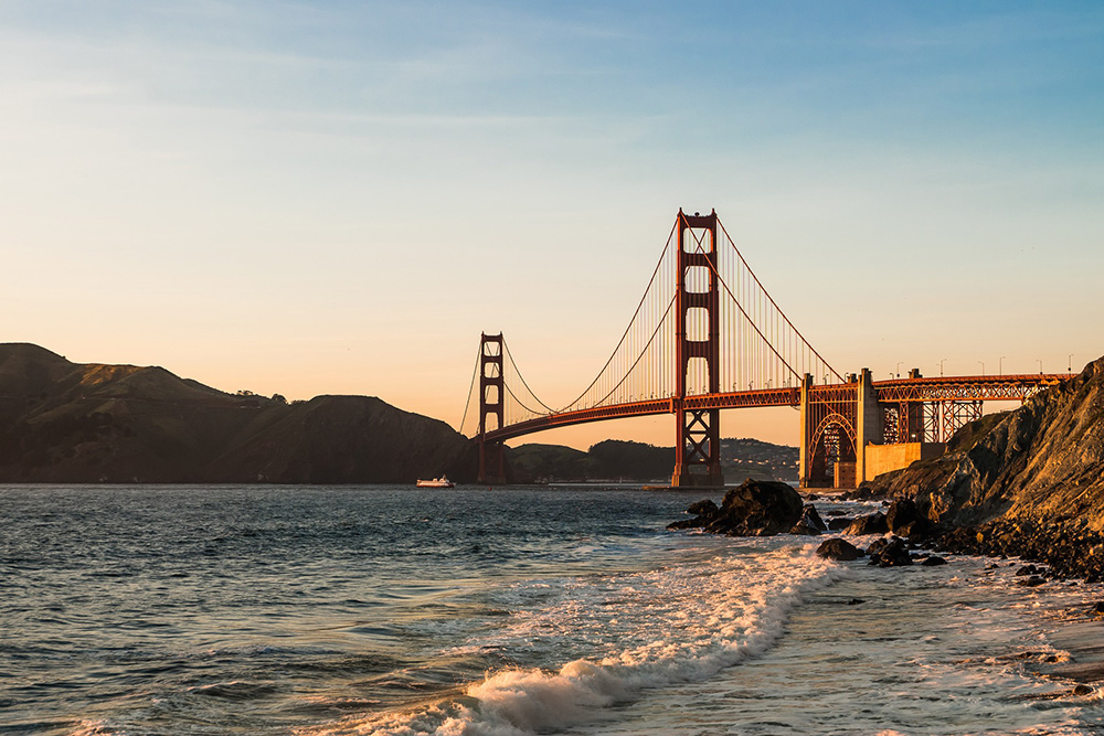 Golden gate Bridge At Sunset With Waves Rolling Up On The Shore.