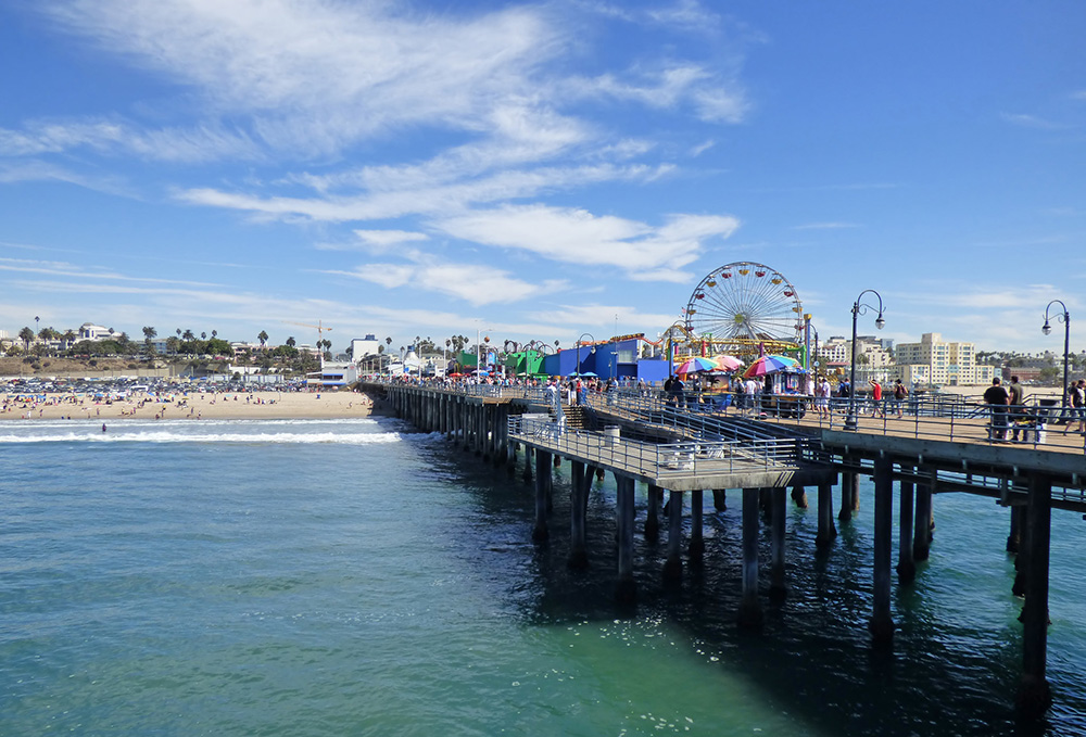 Santa Monica Pier With Vendors And Rides Set Up And People On The Beach.