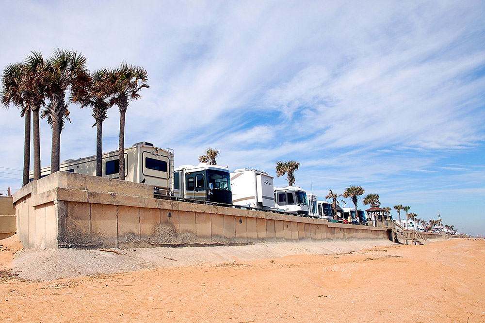 Line OF RVS Parked On A Concrete Lot Overlooking The Beach.