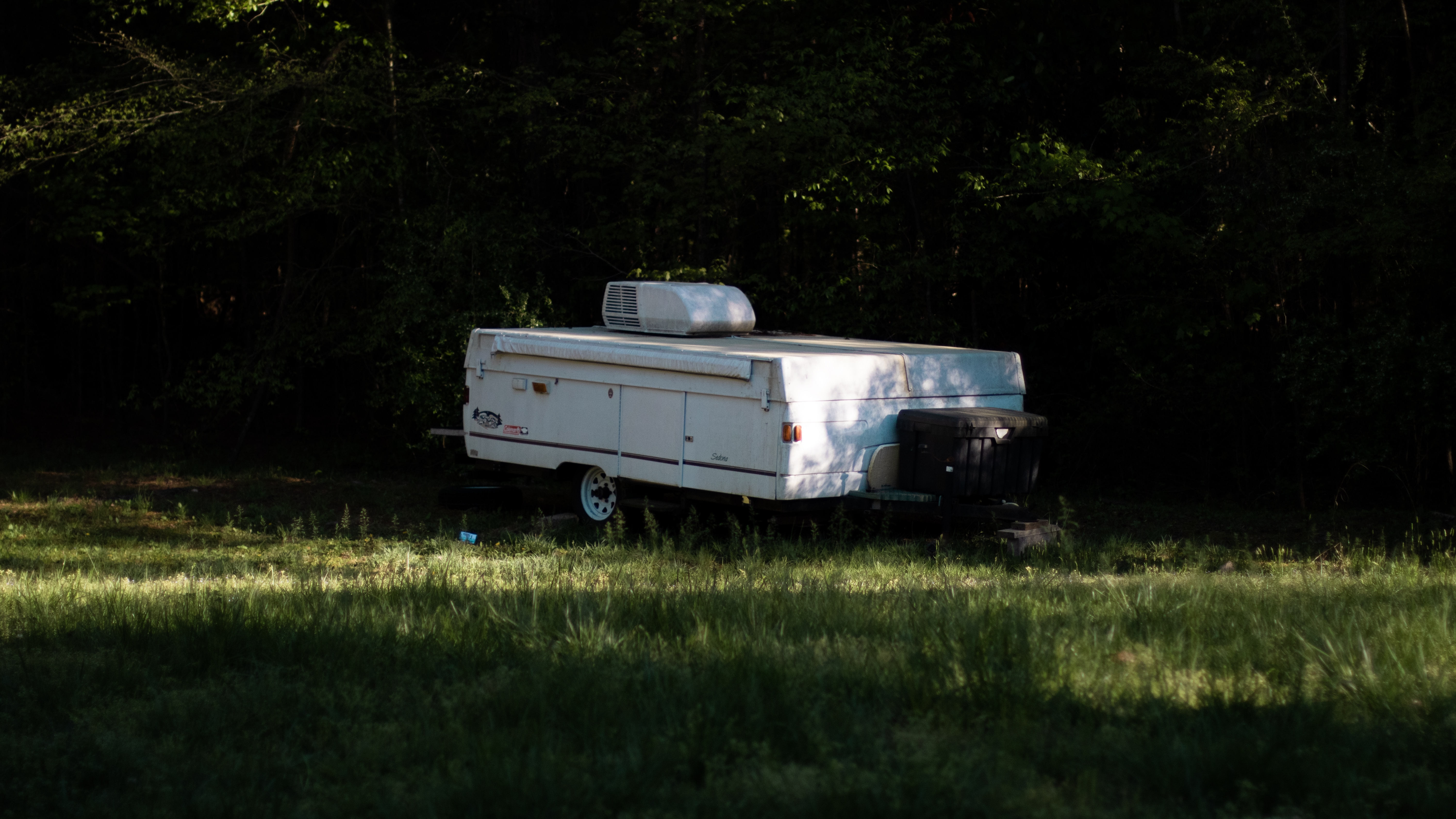 Pop Up Camper Parked In A Field.
