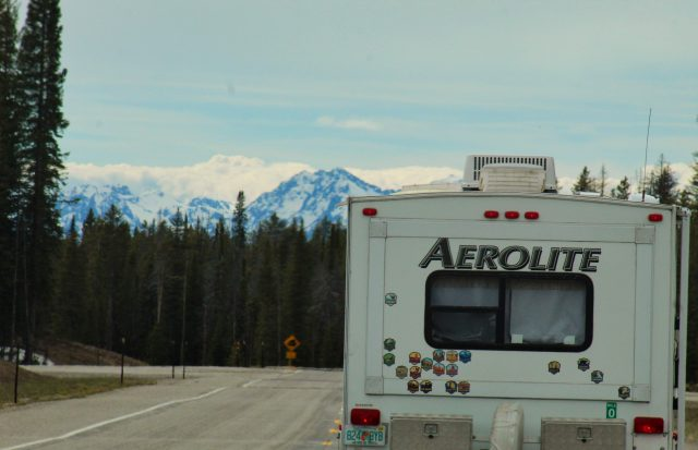 RV Driving Down A Road With A Mountain In The Background.
