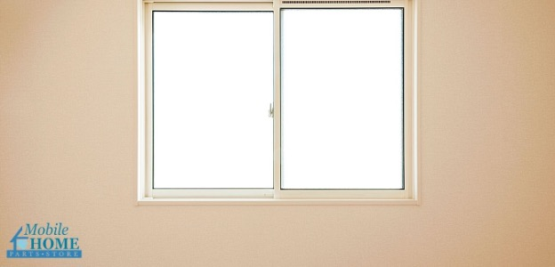 Closed mobile home windows on a beige wall
