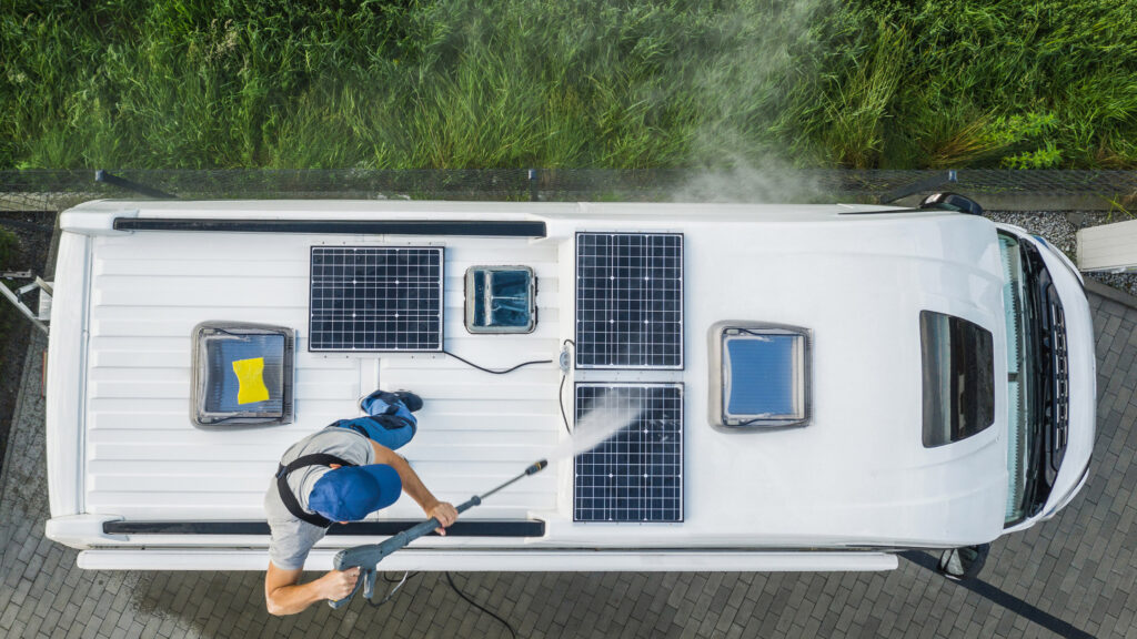 Man standing on the roof of his RV power washing