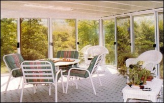 Enclosed All Glass Walled Patio Room With A table And Chairs In The Middle.